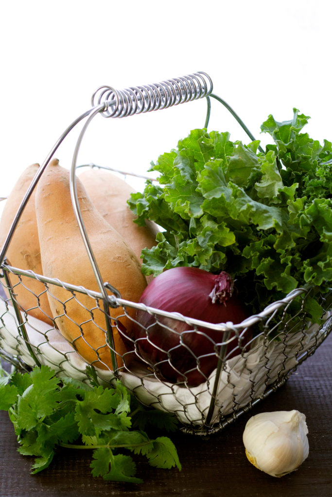 basket of ingredients for vegan stuffed potatoes with black beans and kale