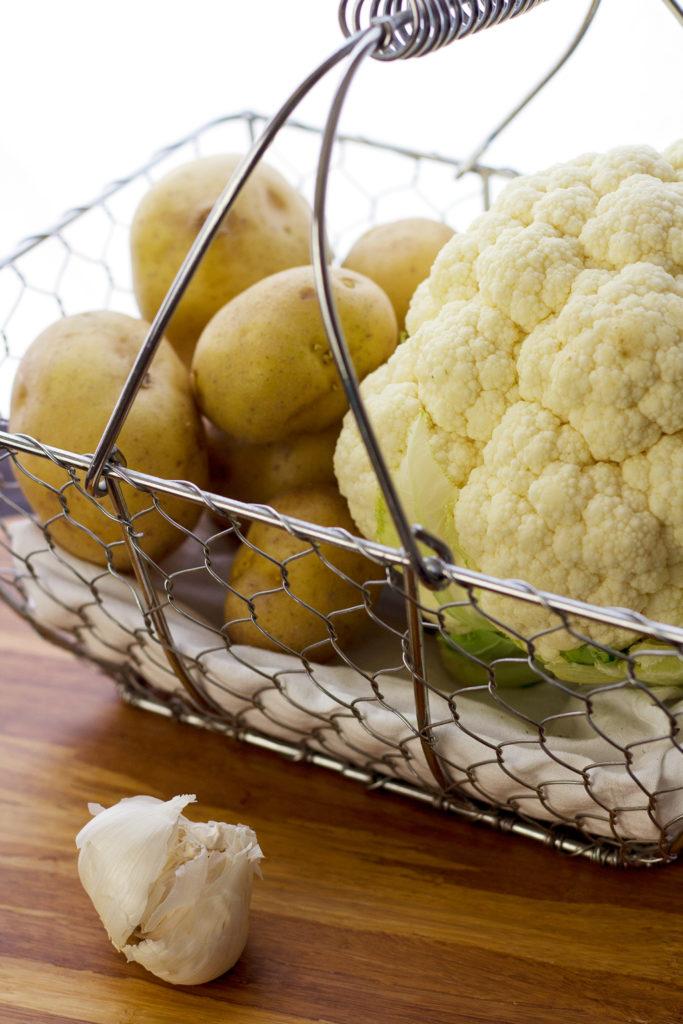 cauliflower and yukon gold potatoes in basket prepping for cauliflower mashed potato recipe