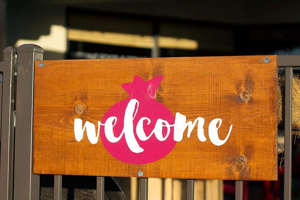 welcome sign at pomegranate cafe in vegan phoenix arizona