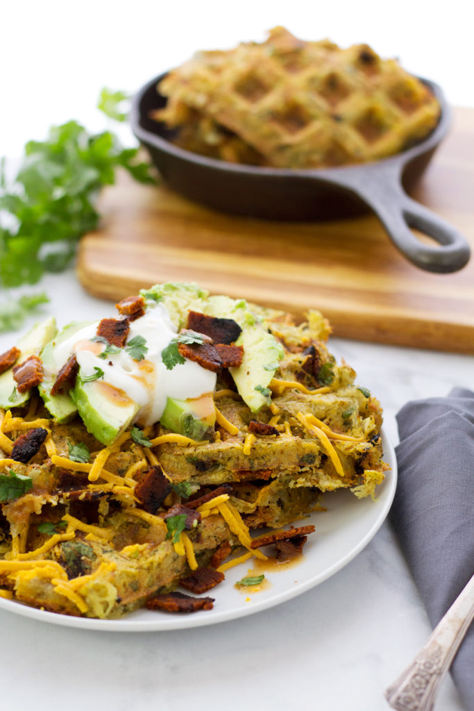 Vegan hash brown waffles topped with mayo, bacon, cheese, and avocado!