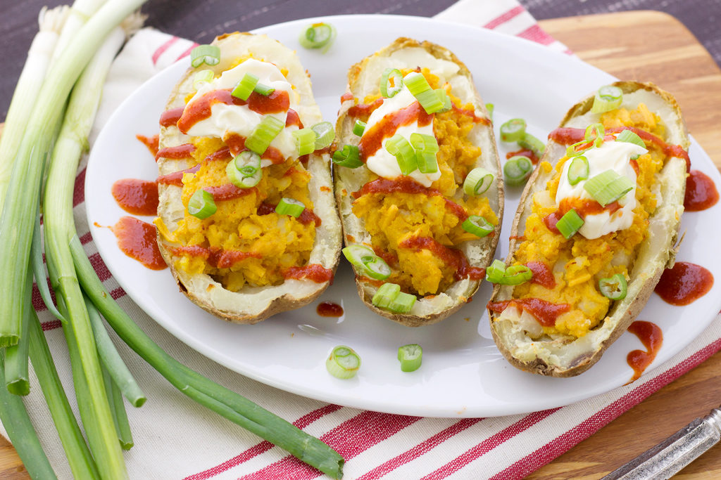 Easy vegan stuffed potato skins with sriracha and nutritional yeast!